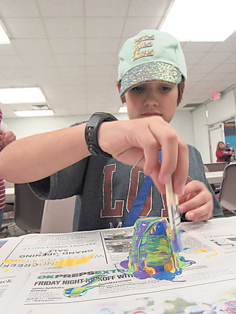 CATHY SPAULDING/Muskogee Phoenix<br /> Eden Perry, 9, swirls multiple colors of paint around a small terra cotta pot Wednesday during a WOW art activity making flower pot monsters at Muskogee Public Library. Muskogee Public Library offers WOW Wednesday activities for youngsters at 4 p.m. each Wednesday.