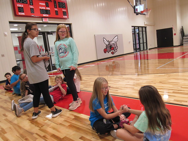 CATHY SPAULDING/Muskogee Phoenix<br /> Hilldale fifth-graders, including, standing, from left, Rylie Johnson, Reese Ellis, and seated, McKenna Price and Avery McWhirt bide their time after physical education class in the new elementary school gym.