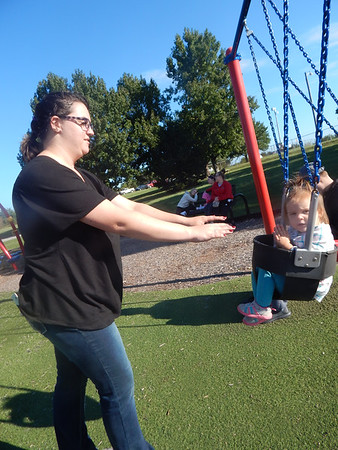 KENTON BROOKS/<br /> Muskogee Phoenix<br /> Muskogee resident Dakota Haney, left, pushes her 2-year-old daughter Eden Ashwood on a swing at Civitan Park on Thursday. The colder weather earlier in the day gave way to warmer, sunny weather and the two were enjoying the sunshine.