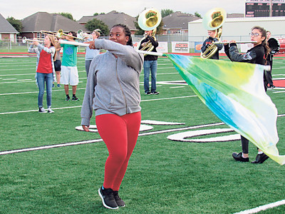 CATHY SPAULDING/Muskogee Phoenix Hilldale High School color guard member Kamyra Mitchell carries her flag while the band practices its football halftime routine.