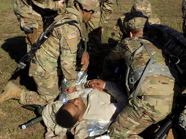 Staff photo by Mike Elswick<br /> Oklahoma National Guard troops practice combat life saver training at Camp Gruber on Thursday. Serving as injured for this exercise is Specialist Johnny Clark of Durant.