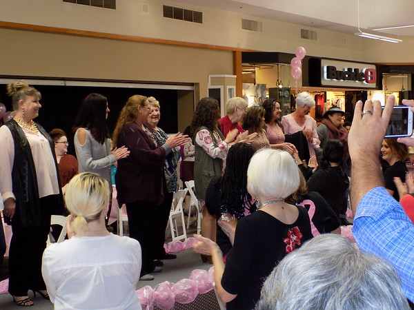 Staff photo by Mike Elswick<br /> Breast cancer survivors serving as models for Thursday's Breast Cancer Awareness lunch andfashion show benefiting Women Who Care take the runway at the conclusion of the fashion show and receive a standing ovation from attendees.