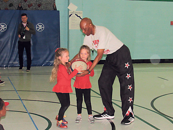 CATHY SPAULDING/Muskogee Phoenix<br /> Former Harlem Globetrotter Valentino Willis gives Tony Goetz Elementary School kindergartners Braylee Brown, left, and Aubrey Brown some basketball tips during an anti-drug/anti-bullying assembly Friday at the school. Willis encouraged students to listen to their teachers, obey their parents and stay away from drugs and alcohol.