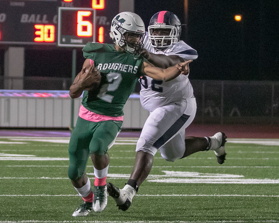 Muskogee's Ty Williams is grabbed by Shawnee's Jesse Ramsey during Friday's game on Creek Nation Field at Indian Bowl. Story in Sports.