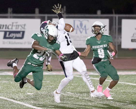 SHANE KEETER/Special to the Phoenix<br /> Muskogee's Jaden Mitchell, left, and Gervorise Warrior, right, break up an intended pass for Shawnee's Jaylon Orange during Friday's game on Creek Nation Field at Indian Bowl. The Roughers won 35-26.