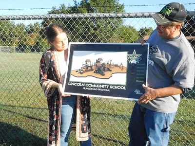 KENTON BROOKS/Muskogee Phoenix Dr. Suzanne Salichs, left, and John Jones, co-founders of Brighter Futures Foundation, hold up the artist's rendering of what the playground at the proposed Boys and Girls Club of Wagoner will look like. They stand at the field where the playground is scheduled to be completed sometime in November.