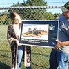KENTON BROOKS/Muskogee Phoenix<br /> Dr. Suzanne Salichs, left, and John Jones, co-founders of Brighter Futures Foundation, hold up the artist's rendering of what the playground at the proposed Boys and Girls Club of Wagoner will look like. They stand at the field where the playground is scheduled to be completed sometime in November.