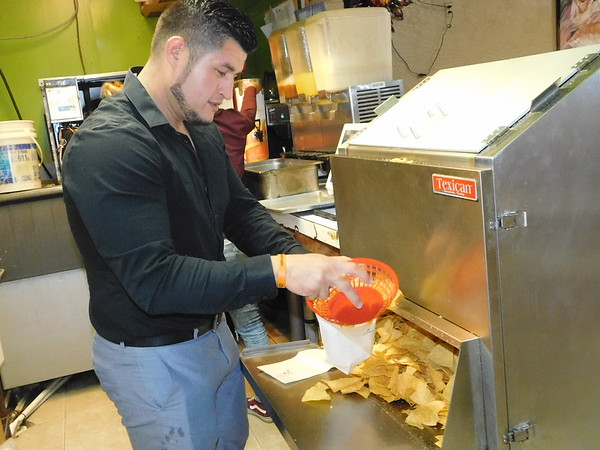 CATHY SPAULDING/Muskogee Phoenix Enrique Gomez fills a bag with tortilla chips at Chavas, a restaurant he opened in 2005.