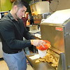 CATHY SPAULDING/Muskogee Phoenix<br /> Enrique Gomez fills a bag with tortilla chips at Chavas, a restaurant he opened in 2005.