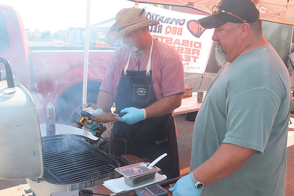 Special photo by Chesley Oxendine<br /> From left, Dan Judd and Jeff Terry prep a competition steak for Saturday's contest in the 'Brew & Bar-B Que.'
