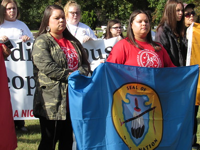 CATHY SPAULDING/Muskogee Phoenix Sisters Britton Cunningham and Lawren Cunningham hold an Osage Nation flag for ceremonies during Indigenous Peoples Day, observed Monday at Honor Heights Park.