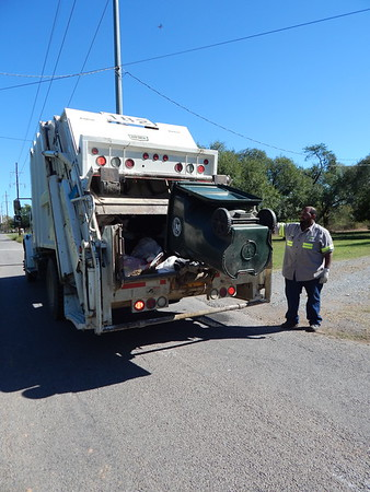 Staff photo by D.E. Smoot<br /> Brandon Current, a municipal sanitation worker, collects garbage Monday along a residential route in Muskogee, where officials plan to take a second look at automating the solid waste collection system.