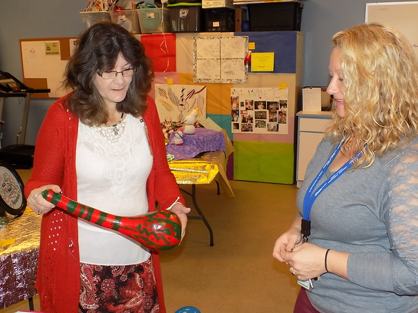 Staff photo by Mike Elswick<br /> DeNisa Howe, left, discusses a hand-painted gourd entered in the Whispering Pines Apartment complex art show with Erin Hester. Hester is executive director of the Muskogee Housing Authority while Howe is resident coordinator at Whispering Pines.