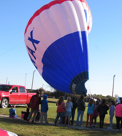 Staff photo by Cathy Spaulding<br /> Creek Elementary students watch a hot air balloon inflate behind their school Wednesday morning.