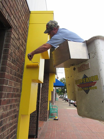 CATHY SPAULDING/Muskogee Phoenix<br /> Tony Swearingen of Superior Paint and Graphics reaches to complete painting around the Muskogee Art Guild entrance on Thursday. Yellow paint around the Muskogee Art Guild entrance adds a splash of color to downtown Muskogee.