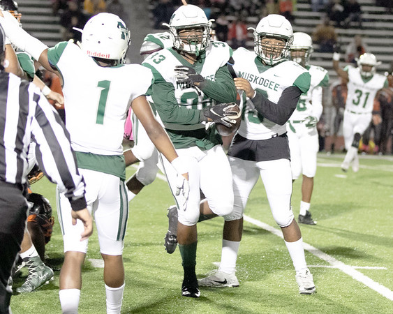SHANE KEETER/Muskogee Phoenix<br /> Muskogee's Kaleb Biglow, center, comes up with the ball after a Booker T. Washington fumble near midfield. Roughers lost to the Hornets 47-26. Story in Sports.