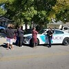 CHESLEY OXENDINE/Muskogee Phoenix<br /> Muskogee Police Officer Veronica Kennedy visits with Kimberly Reynolds (center,) sister of Geoffrey Chaplin, and gathered friends and family Friday afternoon. Chaplin was killed Thursday night after he was struck by a vehicle in the eastbound lane of West Broadway.
