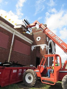 CATHY SPAULDING/Muskogee Phoenix Gilbert Fernandez lifts roofing material to the top of a historic building on the Muskogee Fairgrounds, 1444 S. Cherokee St. The City of Muskogee obtained a building permit for roofing in September.