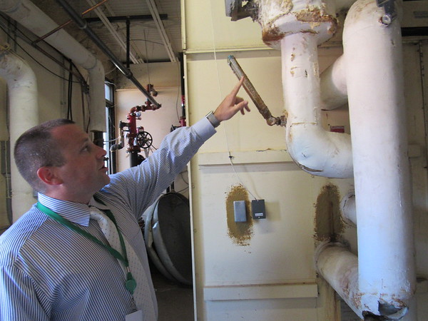 CATHY SPAULDING/Muskogee Phoenix<br /> Muskogee Public Schools Chief Operations Officer Eric Wells shows aging pipes at Muskogee High School.