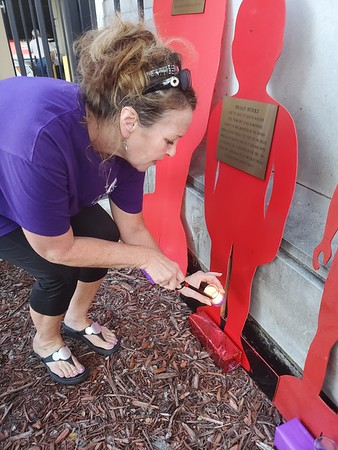 CHESLEY OXENDINE/Muskogee Phoenix<br /> Sheri White lights candles in honor of victims of domestic violence during an event held at the Muskogee County Courthouse on Tuesday evening.