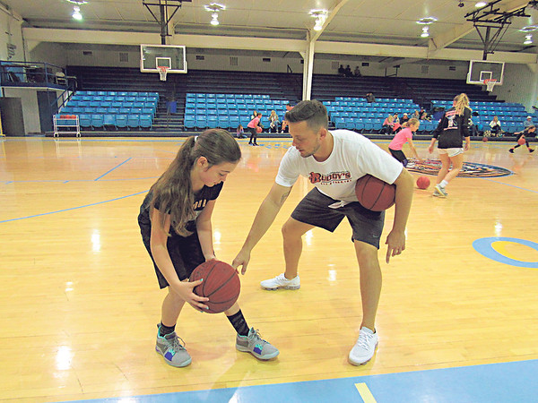 CATHY SPAULDING/Muskogee Phoenix<br /> Oktaha boys basketball coach Kruz Lynch shows fourth-grader Brenlee Moore points on dribbling during a fall break camp at the school Friday.