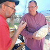Larry Wright of Muskogee Holiness Church offers Mike Lever a snowflake as one of the selections of new food offered.