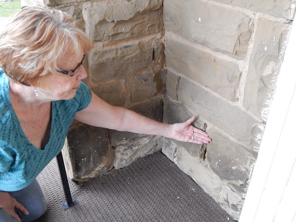 KENTON BROOKS/Muskogee Phoenix<br /> Ann Rossi, a trustee at Warner United Methodist Church, shows the crumbling mortar between the sandstones that make up the church. Rossi and other members know the church is in need of repair, but that doesn't dampen their enthusiasm as they get ready to celebrate the 115th anniversary of the church on Oct. 28.