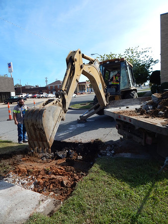 KENTON BROOKS/Muskogee Phoenix<br /> David Davis operates a backhoe and Cerik Martin shovels loose concrete for the city of Muskogee Street Department as they build a wheelchair ramp on South Eighth Street next to the public library on Monday.