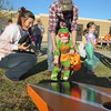 Staff photo by Cathy Spaulding<br /> Brenton Guinn helps his 21-month-old son Jayden Guinn pitch a beanbag while Connors State College agriculture student Brooklyn  Herriman holds more beanbags and cheers Jayden on during Connors Fall Festival on Monday.