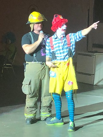 "CHESLEY OXENDINE/Muskogee Phoenix<br /> Muskogee Fire Department Driver Blake Weldon speaks with MFD Private Walker Crow as Crow, dressed as the clown ""Smokey Jr.,"" points into the crowd. The two were part of a larger crew of clowns teaching kids about fire safety Wednesday morning."