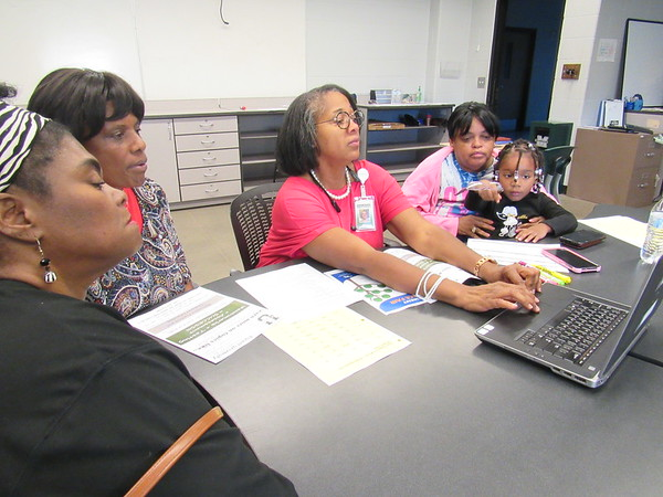 CATHY SPAULDING/Muskogee Phoenix<br /> Muskogee Public Schools parent liaison Lori Jefferson, center, uses her laptop to access information at MPS Parent University. Watching her are, from left, Debbie Williams, Ruby Barker,  Charlsetta Lenzy and 4-year-old Harmonie Brown.