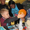 CATHY SPAULDING/Muskogee Phoenix<br /> Damian McFarland, 6, steadies a balloon being inflated by the interaction between baking soda and vinegar while Jonathan Adams watches. First-grade teacher Kimberly Davison holds the bottle. Whittier Elementary students and their parents made several scientific discoveries Thursday during Spooky Science Family Night. The evening included experiments and art about sound waves, chemical reactions and the skeletal system.