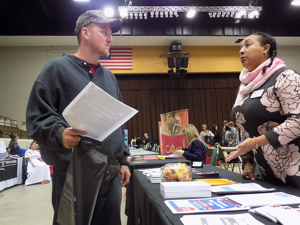 Staff photo by Mike Elswick<br /> Jacob Smith, left, visits with Chris Jones at Wednesday's business and resource fair held at Muskogee Civic Center. Smith was looking a job, while Jones was passing out information on veterans programs of the Oklahoma Employment Security Commission.