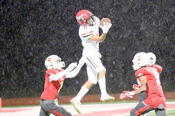 JOHN HASLER/Special to the Phoenix<br /> Hilldale's Troy Maxwell Jr snags the ball out of the air surrounded by three Fort Gibson defenders during Friday's game at Fort Gibson. The Hornets lost 13-6.