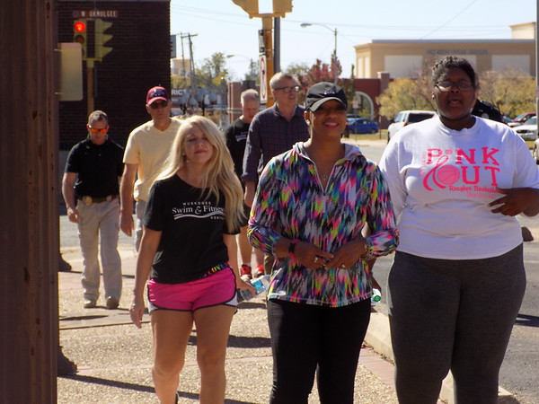 Staff photo by Mike Elswick<br /> A group of participants in Thursday's City of Muskogee 2017 Unity Walk head back to the Hunt's green space along Third Street. The event also was used as a kickoff for the annual Jimmy Moore Memorial Coat Drive with about 50 coats contributed at the event.