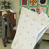Staff photo by Cathy Spaulding<br /> First Lutheran Church member Lillie McNack, watches the Rev. Wayne Schuett, pastor, fold a quilt. Church members make quilts for programs such as WISH and Kids' Space.