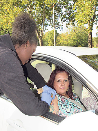 CATHY SPAULDING/Muskogee Phoenix<br /> Indian Capital Technology Center LPN student Jakendra Jackson gives a free flu shot to Delena Ayers. Dozens of drivers — and passengers — passed through Honor Heights Park to get flu shots at Friday's Boo on the Flu. The flu shot clinic was provided by Muskogee Medical Foundation and Saint Francis Muskogee Hospital Auxiliary.