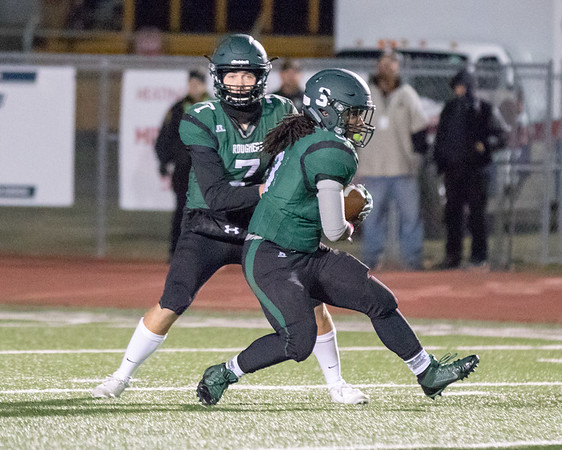 Phoenix special photo by Shane Keeter<br /> Muskogee's Jacob Medrano, left, hands the ball to Kristian Hillmon on Creek Nation Field at Indian Bowl during the Roughers' 27-14 win over Sapulpa on Senior Night on Friday.