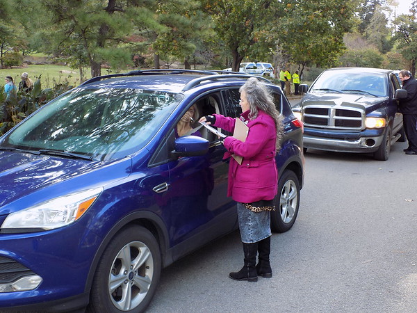 Staff photo by Mike Elswick<br /> Wilma Taylor, in vehicle, is waited on by Veronica Peters to get paperwork filled out for the annual Boo on the Flu drive-through shot clinic Friday morning. Organizers said this was the 22nd year for the event that provides free flu shots as drivers and passengers remained in<br /> their vehicles.