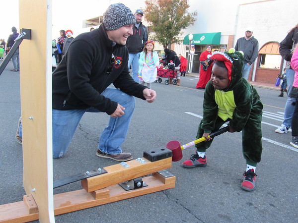 Staff photo by Cathy Spaulding<br /> Jeremy Little of Neighbors Building Neighborhoods, left, encourages Darius Marcul, 4, to keep swinging the mallet at Boo-nanza. Scores of trick or treaters invaded downtown to get candy from businesses, organizations and agencies Saturday during Boo-nanza.