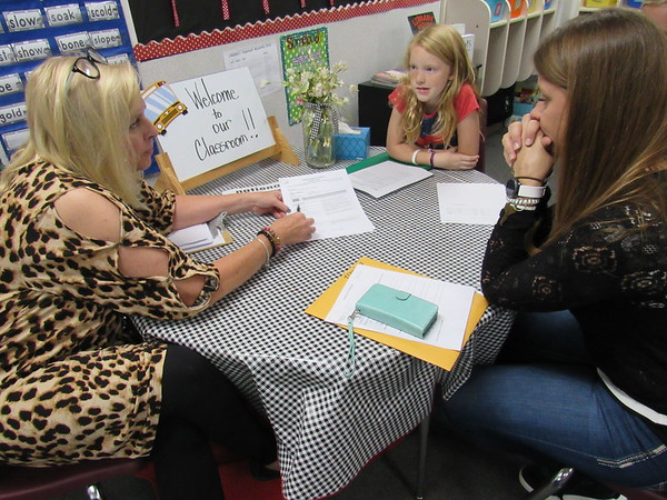 Staff photo by Cathy Spaulding<br /> Third-grade teacher Shawn Dickmann, left, gives Catherine Hardy a report on how well Hardy's daughter, Jessica, performed in school, while Jessica listens. Students take an active part in Fort Gibson parent-teacher conferences.