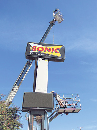 CATHY SPAULDING/Muskogee Phoenix<br /> A crane holds up the lighted sign for a Sonic drive-in while a worker with Claud Neon Federal Signs works on an LED display. The Sonic drive-in at 1921 N. York St., has closed, and its employees have been reassigned to other area Sonics, a corporate spokesperson said.