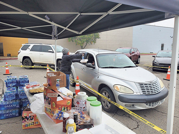 """CHESLEY OXENDINE/Muskogee Phoenix<br /> A volunteer hands out a barbecue plate to a waiting customer during the Okie 101.7 Maples-Washington Family Fundraiser on Tuesday. The """"drive-by BBQ"""" was one of two fundraisers scheduled this week to help Mark and Kim Maples after an Oct. 20 claimed the life of Kim's daughter Kirstey Washington and placed both Kim and Mark in the hospital. The second fundraiser, a benefit concert and silent auction held at the Muskogee Brewing Company, will be Friday. The benefit concert and bean dinner will begin at 5 p.m., while the silent auction will accept bids all day, then close bidding at 8 p.m."""