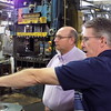Staff photo by Mike Elswick<br /> Muskogee City Councilor Wayne Johnson, left, looks on as Brian Lanham, Acme Manufacturing executive vice president of manufacturing operations, explains processes during a tour of the local industry. The tour was held as part of Business and Industry Week hosted by the Port of Muskogee.