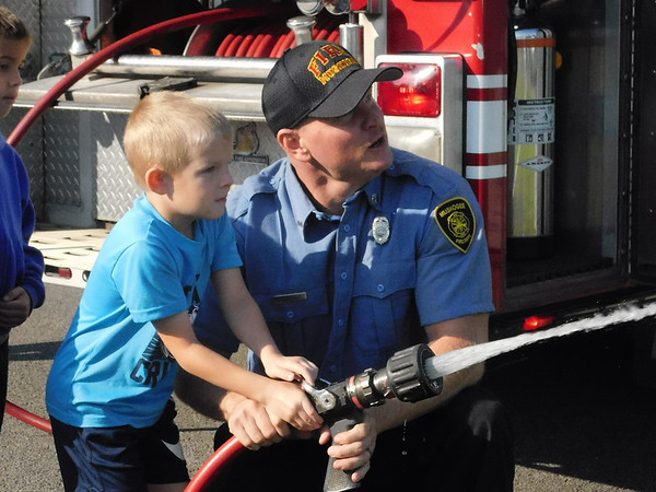 CATHY SPAULDING/Muskogee Phoenix Creek Elementary first-grader Slade Moore sprays a fire hose while Muskogee Firefighter Jeff Lester helps his aim. Muskogee Fire Department brought a pumper unit to the school Friday for Transportation Day.