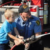 CATHY SPAULDING/Muskogee Phoenix<br /> Creek Elementary first-grader Slade Moore sprays a fire hose while Muskogee Firefighter Jeff Lester helps his aim. Muskogee Fire Department brought a pumper unit to the school Friday for Transportation Day.