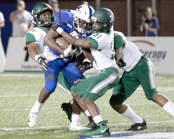 SHANE KEETER/Special to the Phoenix<br /> Rougher defenders Joseph Campbell, left, Jareed Hagerman and Darian Davis, right, work to pull down a Sapulpa runner during Friday's game. Muskogee lost 49-48 in overtime.
