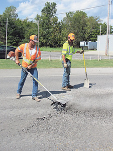 CATHY SPAULDING/Muskogee Phoenix Workers use a rotating wire brush and a shovel to smooth bumps on North Main Street on Friday. The Oklahoma Department of Transportation worked on smoothing a southbound lane of North Main Street, which also is U.S. 64.