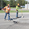 CATHY SPAULDING/Muskogee Phoenix<br /> Workers use a rotating wire brush and a shovel to smooth bumps on North Main Street on Friday. The Oklahoma Department of Transportation worked on smoothing a southbound lane of North Main Street, which also is U.S. 64.