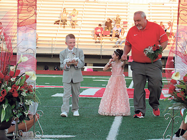 CATHY SPAULDING/Muskogee Phoenix<br /> Fort Gibson High School Principal Gary Sparks escorts his granddaughter, Parker<br /> Hancock, down the 50-yard line as Rhett Wicks carries the crown for Fort Gibson's all-school homecoming queen coronation Friday. Parker was the coronation's flower girl.